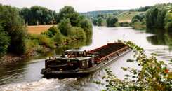 Barge on an inland waterway lined with trees